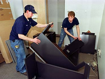 Office movers assembling furniture